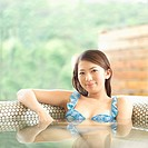 Young woman in bikini sitting in pool, looking at camera, smiling