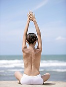 Topless young woman on beach in yoga position