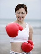 Young woman in boxing gloves on beach
