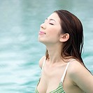 Young woman in bikini swimming in water, eyes closed