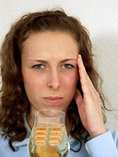 Woman taking tablets with alcohol, glass of white wine