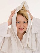 Young woman mit white bathrobe drying her hair with towel