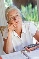 Elderly lady with documents and calculator