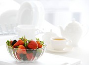 Glass bowl of strawberries and blackberries on table, tea set aside