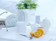 Tea set, dishes and oranges on kitchen table, close_up