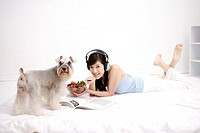 Young woman lying on bed with headphones, holding bowl of strawberries, Wire Fox Terrier standing aside