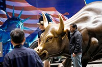 Standing by bronze statue of charging bull, Bowling Green park, Wall Street, New York, USA