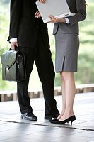 Businessman and businesswoman standing on train platform, low section