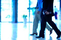 Businessmen walking in lobby, low section