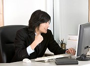 Businessman using computer at desk, cheering, side view