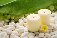 Burning candles, frangipani and banana leaf on pebbles