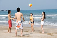 Four young adults playing ball on beach