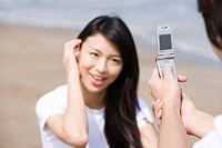 Young man taking photograph of young woman with mobile phone