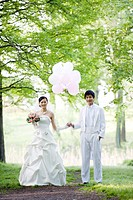 Young bride and groom holding balloons outdoors, smiling