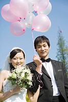 Bride and groom holding balloons, smiling