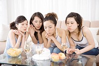 Four young women blowing out candles