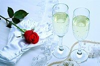 Single rose, pearl necklace, white glove and wineglasses with beer