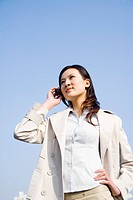 Young businesswoman talking on mobile phone against blue sky