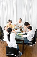Three generation family eating meal