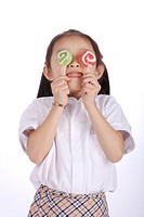 Girl 6_7 holding two Lollipop over eyes, close_up
