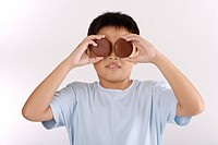 Boy holding two biscuits over eyes, close_up