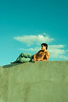 Barechested young man reclining on ledge, low angle view