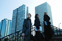 Three women dressed in black walking up steps, all carrying laptop computers, high rises in background