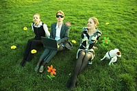 Three females sitting side by side with dog in field with flowers, one using laptop computer, high angle view
