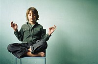 Boy sitting in lotus position in chair, eyes closed