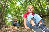 Four and six year old brothers on seated on walking trail in forest, Winnipeg, Canada