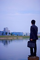 Young businessman standing at water´s edge