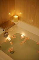 Bathtub full of water and petals with burning candle on the edge