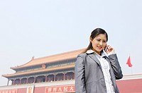 Business woman on the phone before Tiananmen Square