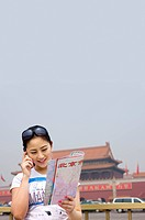 Young woman on the phone holding a map in her hand