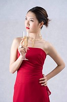 Young woman wearing a red evening gown, holding a glass of champagne, hand on hip
