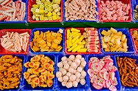 A variety of meatballs and fish balls in trays, on display at a market stall