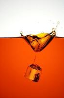 An ice cube dropping into black tea, tea splashing upwards