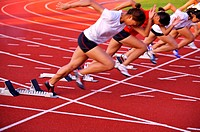 Female athletes running on race track