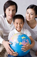 Family with one child looking at the camera and holding the globe