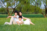 Young family with one child sitting on the lawn and looking at the camera