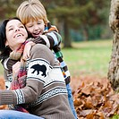 Young boy embraces mother from behind, outdoor in autumn, Vancouver, British Columbia