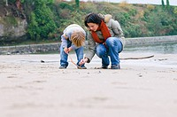Woman and boy examine objects on beach, Vancouver, British Columbia