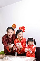 Young family with one child in traditional clothes showing dumplings and smiling at the camera