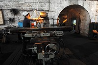 Woman technician working next to lathe in old stone factory space built in 1937, Dongfeng Electric Machinery Works Company, Leshan City, Sichuan Provi...