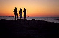 drei Menschen stehen am Meer und beobachten den Sonnenuntergang / three people standing on the shore watching the sunset