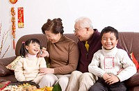 Elderly couple with two children sitting on the sofa and smiling happily