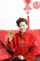 Mature adult woman in traditional clothing sitting on the sofa, holding a moon cake and smiling at the camera