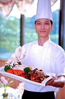 Chef holding a serving dish and looking at the camera