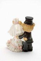 Close_up of two figurines of bride and groom holding together