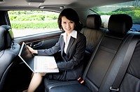 Businesswoman sitting in the car and using laptop